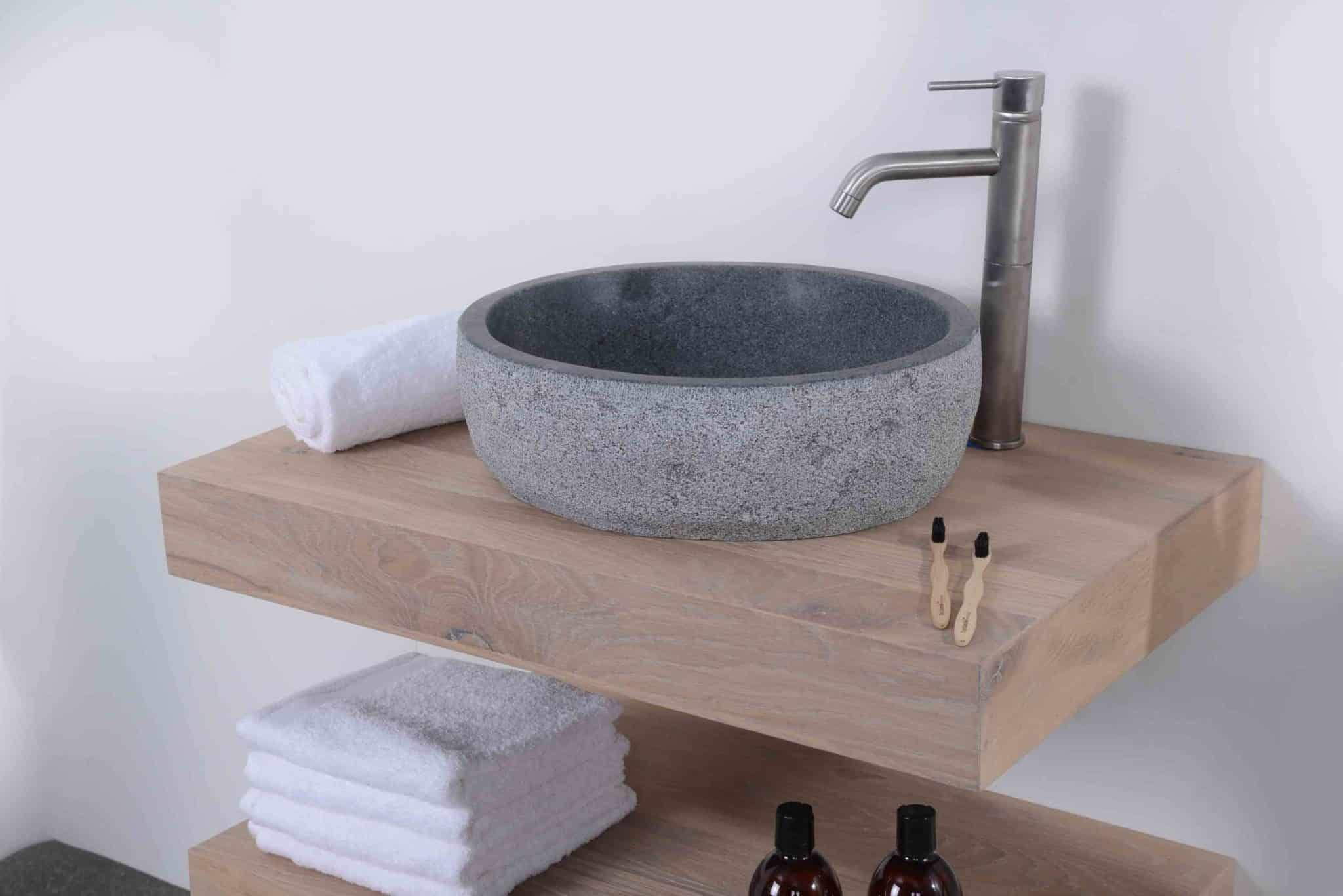 mooie rvs kraan boven een granieten waskom op een eiken wastafelblad