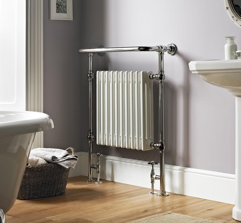 klassieke handdoek radiator in de badkamer naast een bad op pootjes
