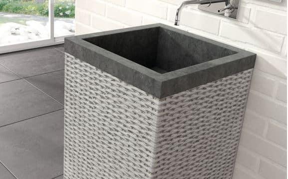 grijze waskom van natuursteen met een inbouw wastafelkraan