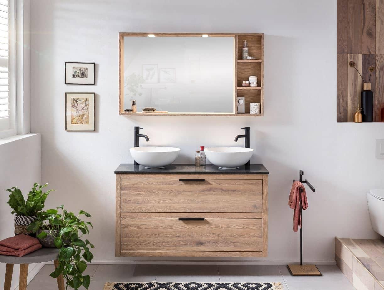 badkamermeubel op maat in de badkamer met bijpassende spiegel en zwarte kranen