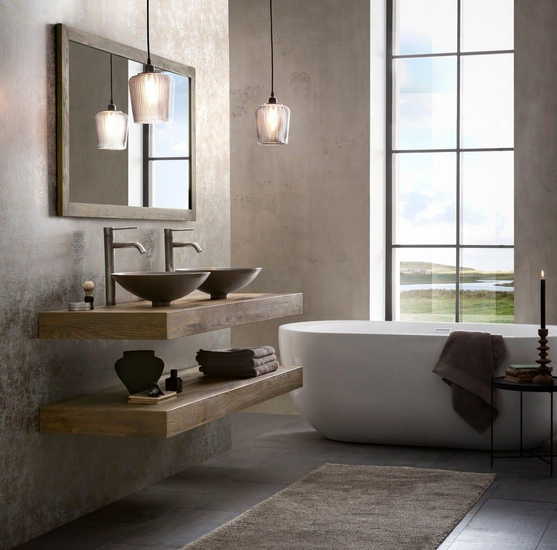 vrijstaand bad met een houten badkamermeubel