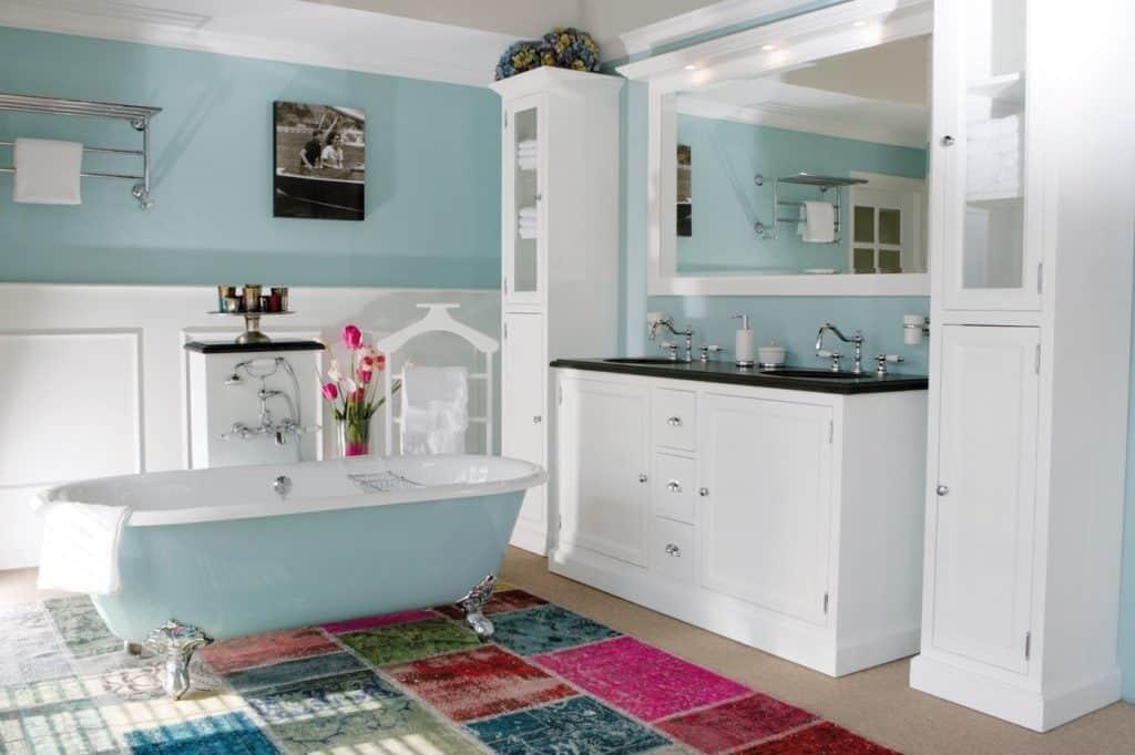 landelijke badkamer in het wit met bad op pootjes en twee bijpassende kolomkasten