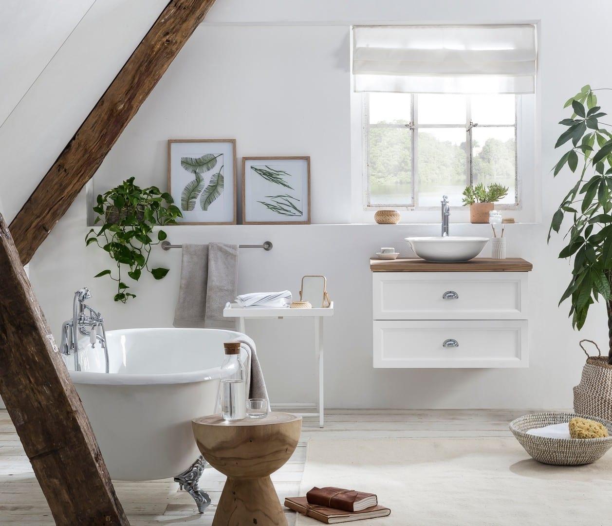 landelijke badkamer met eiken wastafelblad op het landelijke badmeubel met een vrijstaand bad op pootjes