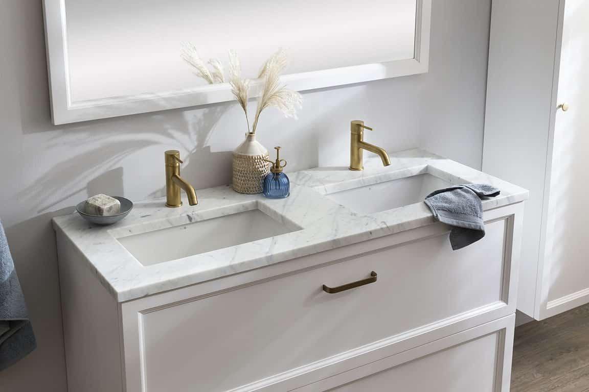 een klassiek badkamermeubel met twee ingebouwde waskommen en gouden kranen.