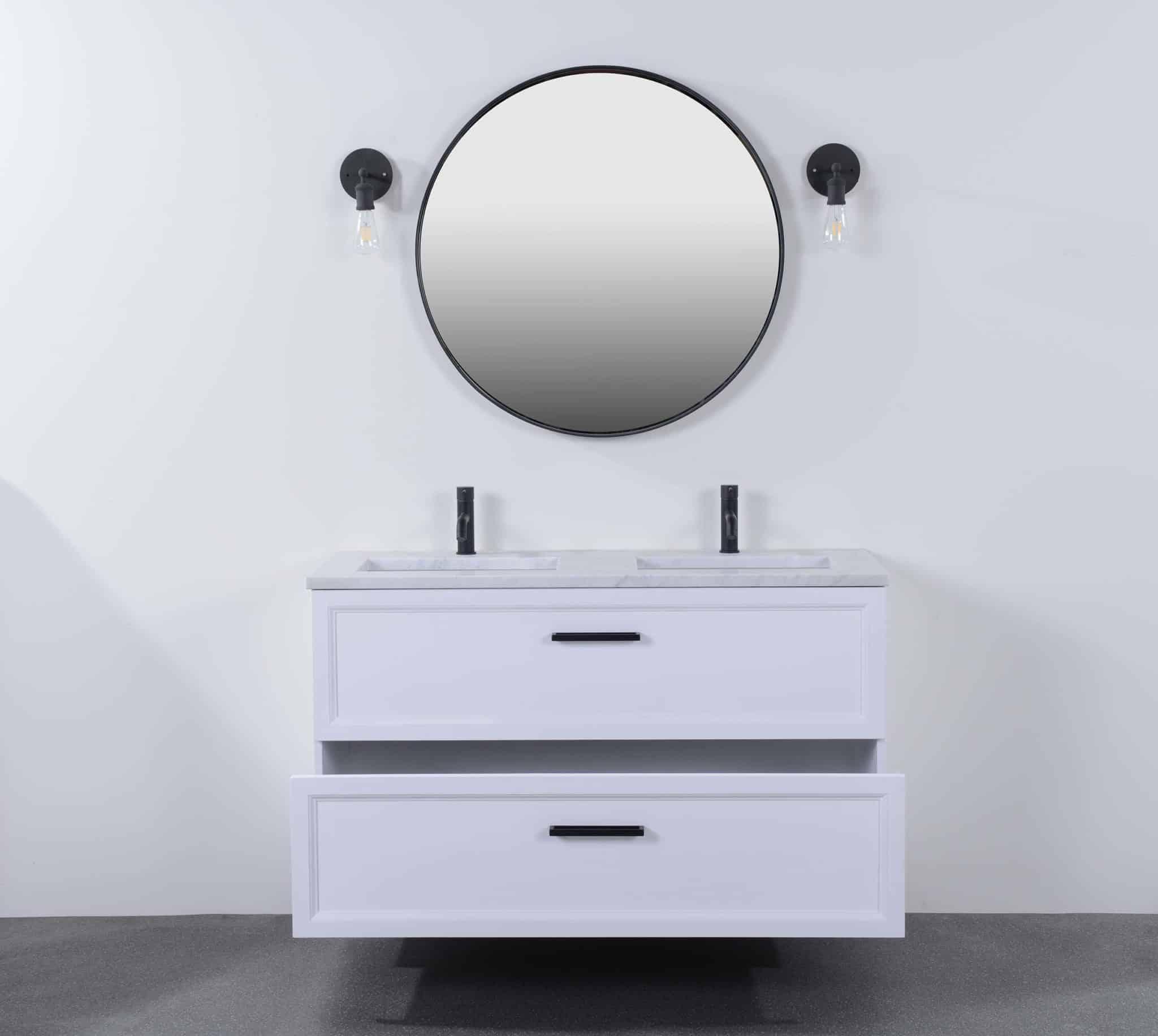 een wit gespoten badmeubel met zwarte kranen en een ronde spiegel