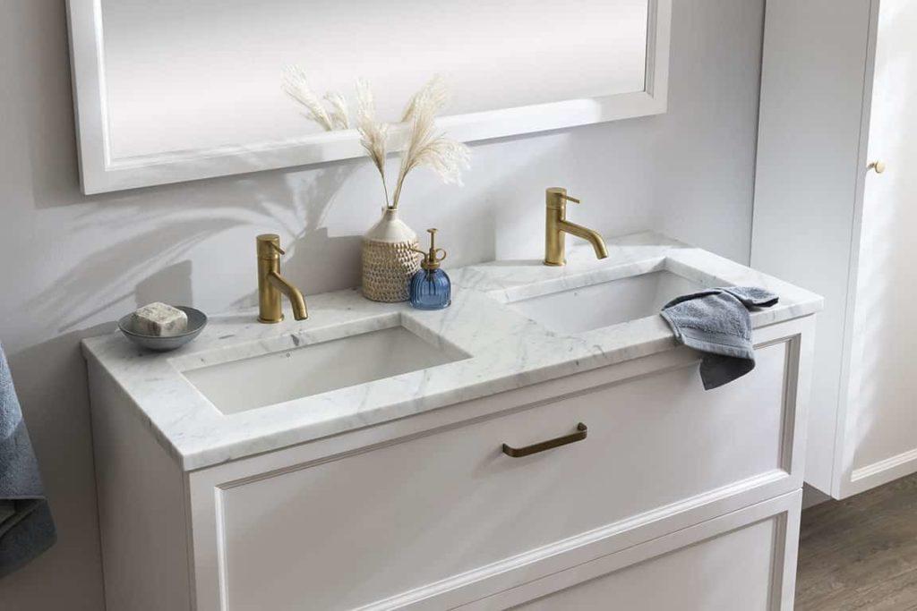 Klassiek badkamermeubel met gouden kranen en een marmeren wastafelblad