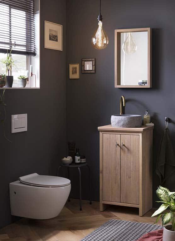 Staand WC meubel van massief eiken met een granieten waskom en gouden kraan. Boven het toiletmeubel is een bijpassende eiken spiegel geplaatst