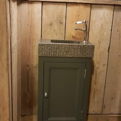 donker toiletmeubel industriële sfeer met robuuste wastafel en fonteinkraan