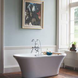 wit vrijstaand bad met een klassieke badkraan in de landelijke badkamer