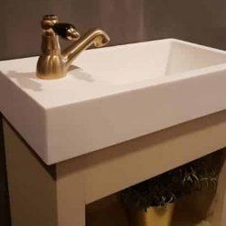 toiletmeubel met keramische wastafel en een gouden fonteinkraan