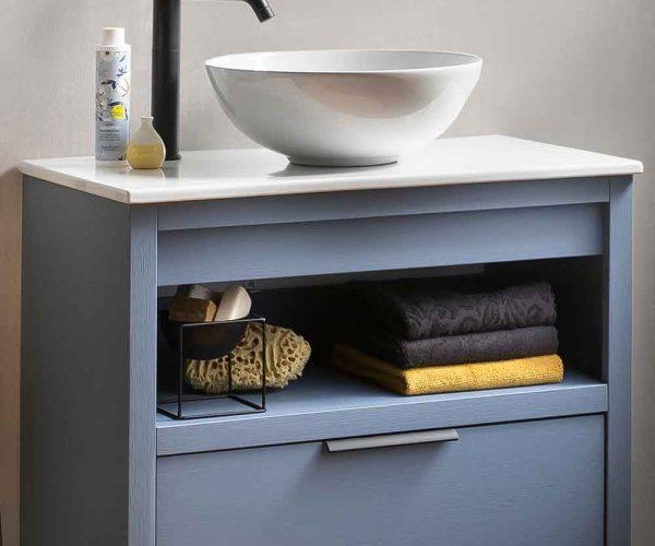 badmeubel met een onderkast, een zwarte kraan en een keramische waskom.