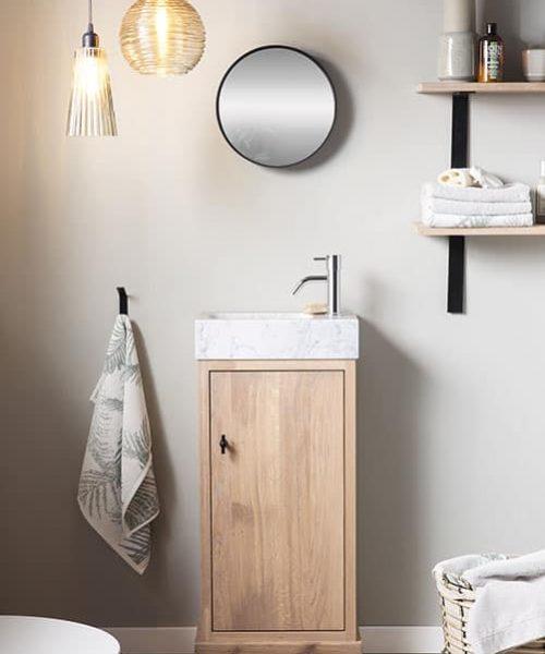 landelijk toiletmeubel van massief eiken met een marmeren wastafel en een zwarte spiegel