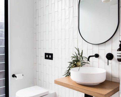 mooi industrieel badkamermeubel met witte waskom en zwarte spiegel