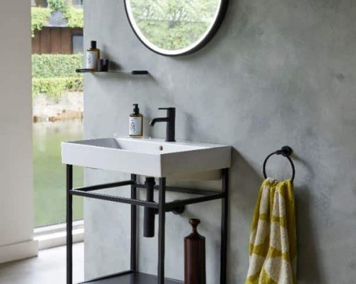 industrieel badkamermeubel op poten met een witte wastafel en een zwarte spiegel