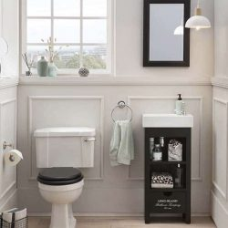 klassieke toiletruimte met daarin een zwarte fonteinkast met een witte wastafel en een zwarte spiegel