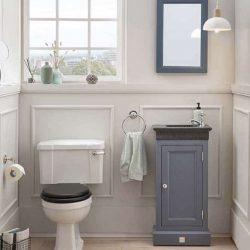 staand toiletmeubel van massief hout met granieten fontein en bijpassende spiegel in de toiletruimte