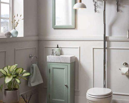 landelijke fonteinkast in groen met een bijpassende spiegel en klassiek toilet in de toiletruimte