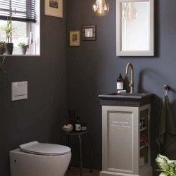 WC meubel met granieten fontein en gouden kraan met bijpassende spiegel met hangend toilet in de toiletruimte