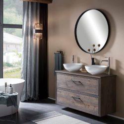 Hangend badmeubel van massief eiken met een eiken wastafelblad, twee keramische waskommen en boven het badmeubel is een ronde zwarte spiegel geplaatst.
