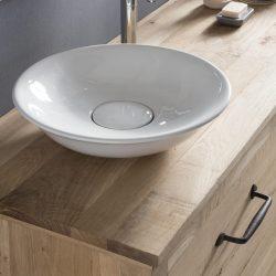 keramische waskom op een eiken badmeubel met een mooie wastafelkraan