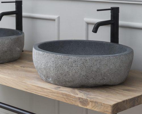 Badkamermeubel met granieten waskom en zwarte kraan.