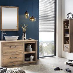 een houten badmeubelnmet een landelijke kraan en een houten spiegel.