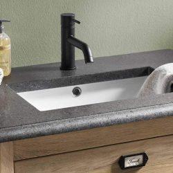 een houten badkamermeubel met een granieten wastafelblad en een zwarte kraan