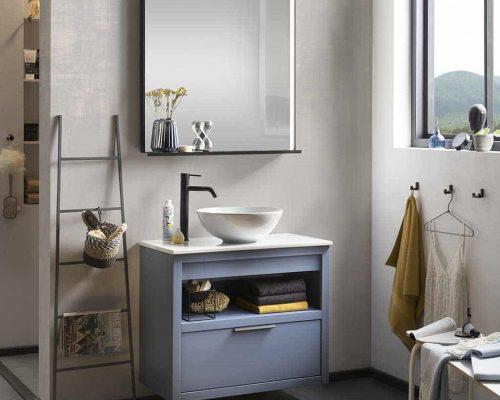 een blauw gespoten badkamermeubel met een keramische waskom, een spiegel en een zwarte kraan
