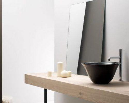 zwarte waskom op een eiken wastafelblad in de badkamer