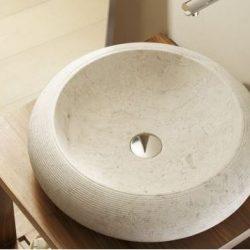 lichte waskom van natuursteen in de badkamer