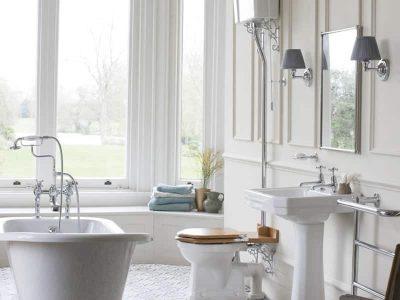 Een klassieke badkamer met een hooghangen toilet, keramieke wastafel en een vrijstaand bad op pootjes