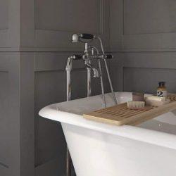 klassieke badkraan met zwarte handvaten bij een vrijstaand bad op pootjes