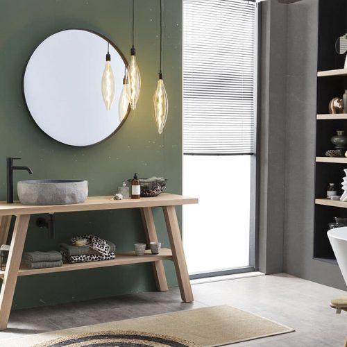 landelijke wastafel met een opzetwaskom, een zwarte kraan en een spiegel.