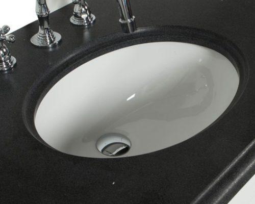 mooie keramische ovalen wastafel onder een granieten wastafelblad in een badkamer