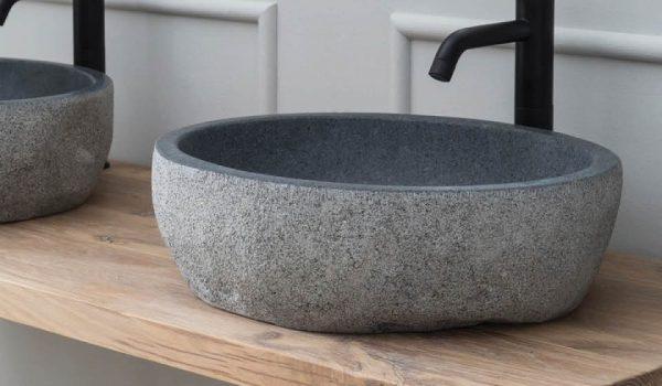 granieten waskom op een badkamermeubel met een zwarte kraan