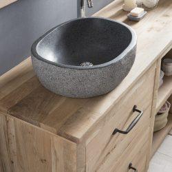 mooie ovalen waskom van graniet op een eiken badmeubel
